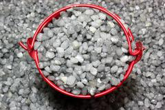 Gray gravel for construction and red bucket - stock photo