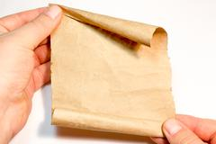 The sheet of parchment in hand on white background Stock Photos