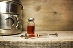 Glass Syringe, ampoule on a wooden table - stock photo