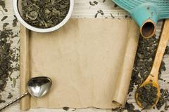 Sheet of parchment, green dry tea and kettle on wooden table Stock Photos