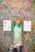 Boy in front of paint splattered wall Stock Photos