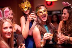 Young women with drinks wearing masks at hen party - stock photo