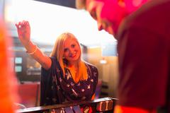 Woman standing in front of disc jockey's mixing desk Stock Photos
