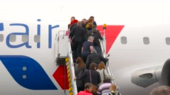 Passengers boarding to airplane up the airplane steps Stock Footage