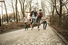 Five teenagers fooling around in park - stock photo