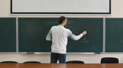 The young manager reports and draws the graph on the blackboard - stock footage