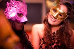 Young women wearing masquerade masks at hen party - stock photo
