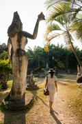 Woman walking past statue, Xieng Khu, Vientiane, Laos - stock photo
