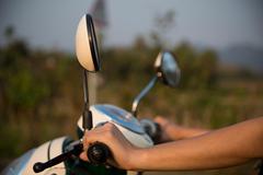 Woman's hands on moped handlebars - stock photo