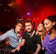 Disc Jockey surrounded by group of people Stock Photos