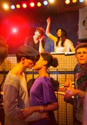 Young couple kissing at party, disc jockey in background Stock Photos