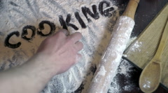 Cooking concept.  Finger writting word cooking on wheat flour. Background Stock Footage