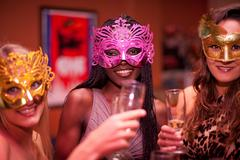 Young women wearing masquerade masks at hen party Stock Photos