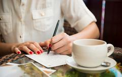 Woman writing postcard in cafe - stock photo