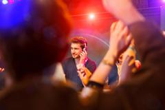 Disc jockey surrounded by people dancing Stock Photos