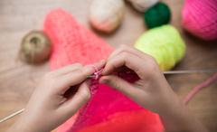 Baby girl knitting pink scarf close up Stock Photos