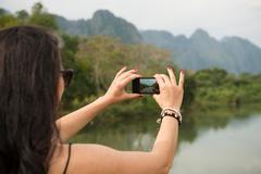 Woman using camera phone, Nam Song River, Vang Vieng, Laos Stock Photos