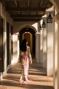 Woman walking past columns in hotel - stock photo