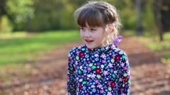 Beautiful little girl talks and gesticulates in sunny autumn park Stock Footage