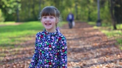 Beautiful little girl grimaces and laughs in autumn park - stock footage