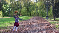 Beautiful little girl in skirt throws up dry leaves and in autumn park - stock footage