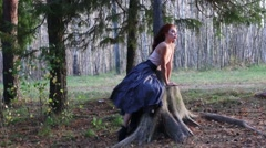 Beautiful girl sits on big stump and poses in autumn forest Stock Footage