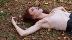 Beautiful girl lies on dry leaves in skirt in autumn forest - stock footage