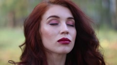Close up view of beautiful girl with closed eyes opening lips and eyes in for Stock Footage