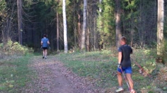 Back of three men running with sticks on path in autumn forest - stock footage