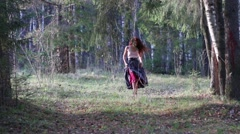 Pretty girl in grey skirt goes in sunny autumn forest - stock footage