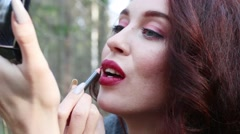 Pretty smiling girl makes up outdoor, close up view Stock Footage
