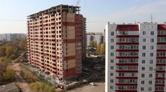 Pink residential building and brick building under construction Stock Footage