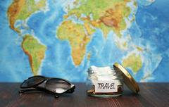 Travel money in  jar, sunglasses, world map at  background. Stock Photos