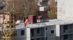 Crane lifts heavy load and people work on construction site - stock footage