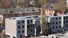 Construction site with moving crane and part of concrete panel building Arkistovideo