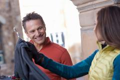 Mature man and young woman clothes shopping, smiling Stock Photos