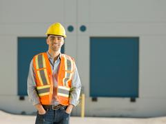 Mid adult construction worker with hand sin pockets, portrait Stock Photos