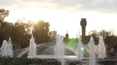 Fountain with many splashes and sun in autumn city Stock Footage