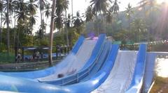 Boy Having Fun Sliding Down a Water Slide at Swimming Pool. Slow Motion. Stock Footage