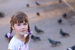 Little pretty girl with pigtails smiles and looks at camera near pigeons on a - stock photo