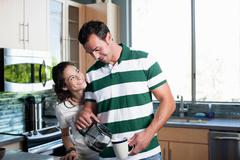 Young couple pouring coffee from pot in kitchen, smiling Stock Photos