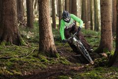 Mountain biker riding through trees - stock photo