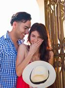 Young man looking at woman giggling, portrait - stock photo