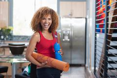 Mid adult woman in holding yoga mat and water bottle, portrait - stock photo