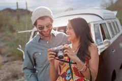 Young woman holding camera with boyfriend on road trip, smiling - stock photo