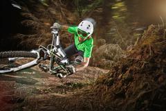 Mountain biker riding narrow track - stock photo