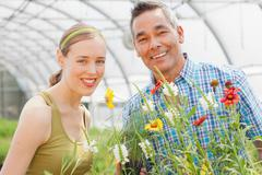 Mature man and mid adult woman shopping in garden centre, smiling Stock Photos