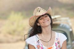 Young woman in cowboy hat wearing earphones, smiling - stock photo