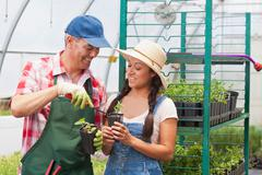 Mature sales assistant advising young woman in garden centre Stock Photos