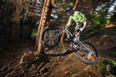 Mountain biker mid air above forest path - stock photo
